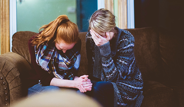 A woman comforting a friend as she grieves